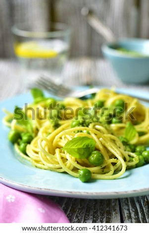 Spaghetti with green peas and basil pesto on a blue plate on old wooden table. - stock photo
