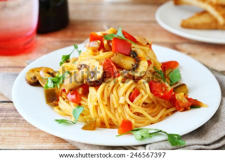 Spaghetti with mushrooms and peppers on a white plate, food - stock photo