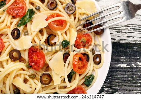 Spaghetti with olive sauce on white plate - stock photo