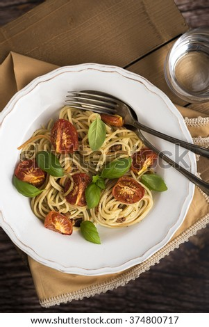 Spaghetti with roasted tomatoes and basil leafs into vintage plate - stock photo