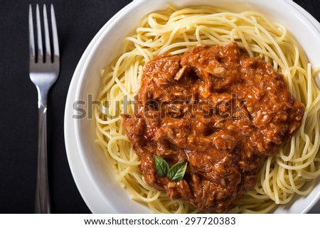 Spaghetti with Tuna sauce over black background - stock photo