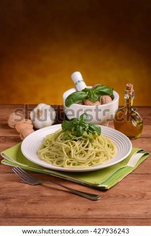spaghetti with walnut pesto with ingredients around - stock photo