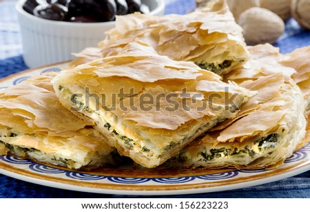 Spanakopita, Greek spinach pie with feta cheese and filo party on on plate with olives and walnuts on festive plate - stock photo
