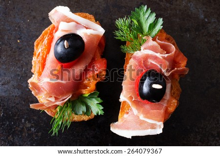 Spanish appetizer with jamon on a black background top view - stock photo