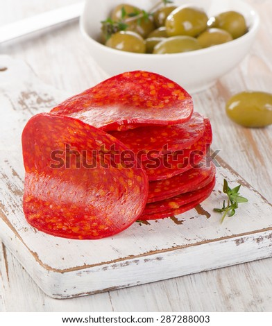 Spanish chorizo sausage with herbs on  wooden chopping board. Selective focus - stock photo