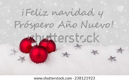 spanish Christmas card with red christmas tree balls and text Merry Christmas and a happy New Year/Merry Christmas and a happy New Year/spanish  - stock photo