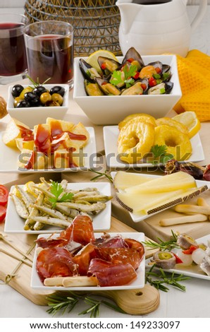 Spanish cuisine. Assortment of  Tapas including Serrano Ham, Manchego Cheese, Marinated Olives, Pickles, Potatoes in Hot Sauce, and others, served with red wine. - stock photo