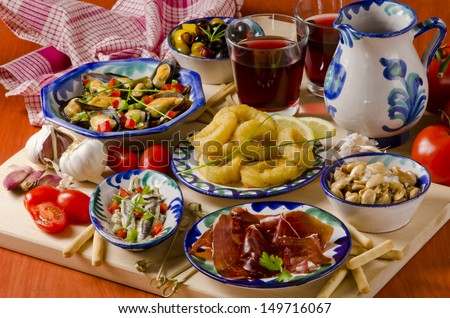 Spanish cuisine. Assortment of  Tapas including Serrano Ham,  Marinated Olives, Mussels in Sauce and others, served with red wine. - stock photo