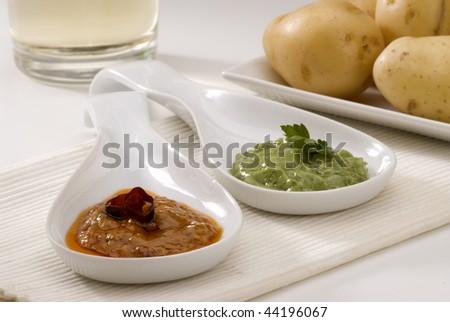 Spanish cuisine. Green mojo and red mojo sauce served in a white bowl. Typical Canary hot sauce. Mojo verde y mojo picon. Selective focus. - stock photo