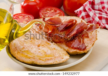 Spanish cuisine. Olive oil pouring over sliced  tomato bread. Selective Focus. Pa amb tomaquet i pernil. - stock photo