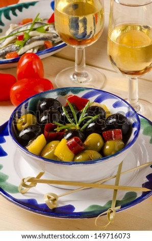 Spanish cuisine. Tapas. Marinated Olives in a ceramic plate.Two glasses of Sherry Wine in background. Selective Focus. - stock photo
