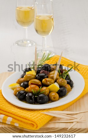 Spanish cuisine. Tapas. Marinated Olives in a white plate.Two glasses of Sherry Wine in background. Selective Focus. - stock photo