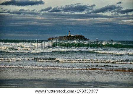 Spanish destination on Atlantic Ocean, Somo beach in Cantabria region, view on lighthouse - stock photo