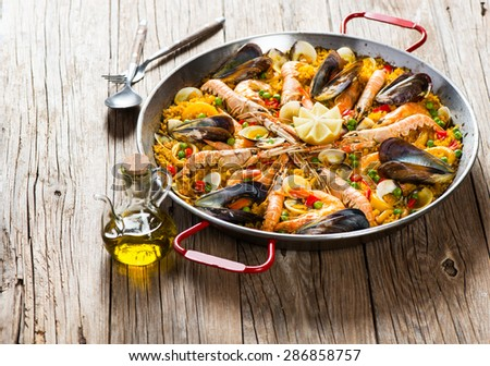 Spanish dish paella with seafood  in traditional pan on a rustic wooden table - stock photo