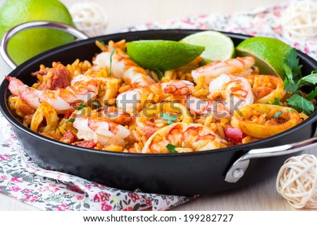 Spanish dish paella with seafood, shrimps, squid, rice, saffron, traditional tasty dinner - stock photo