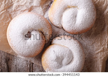 Spanish ensaimadas sweet rolls with powdered sugar close-up on the table. horizontal view from above - stock photo