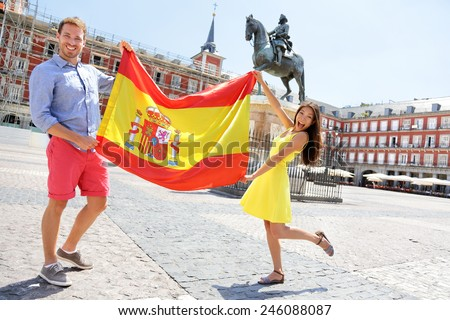 Spanish flag. People showing Spain flag in Madrid on Plaza Mayor. Happy cheering celebrating young woman and man holding and showing flags to camera on the famous square. - stock photo