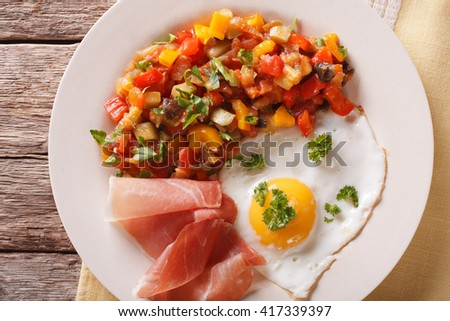 Spanish Food: fried egg, ham and vegetables Pisto on the plate closeup. Horizontal view from above