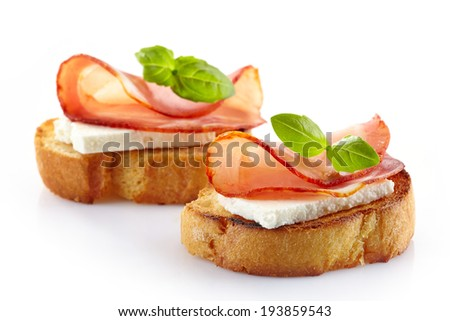 Spanish food tapas. Toast with fresh goat cheese and smoked serrano meat - stock photo