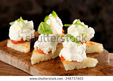Spanish food tapas. Toasted bread with fresh cheese and vegetables - stock photo
