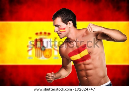 Spanish football fan is ready for fight over spanish flag background - stock photo