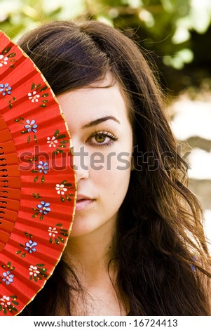 Spanish green eyed woman behind traditional fan. - stock photo