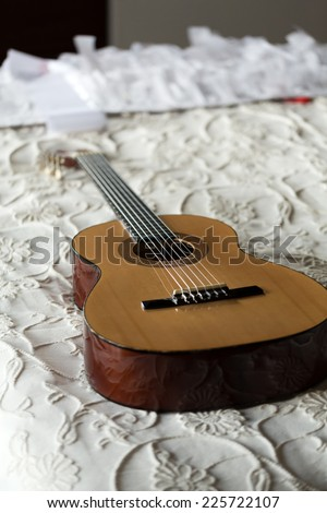 Spanish guitar lying on the bed - stock photo