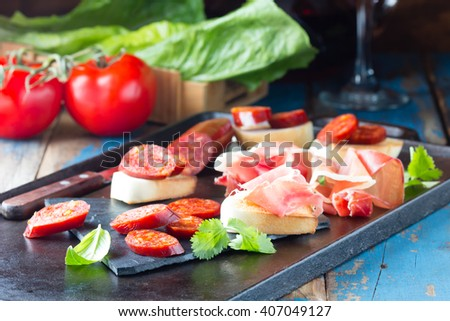 Spanish Ham and salami with bread accompanied by glass of red wine pn black table. Jamon Serrano  - stock photo