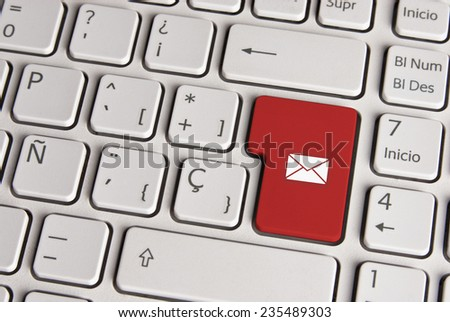 Spanish keyboard with email concept mail envelope icon over red background button. Image with clipping path for easy change the key color and editing.