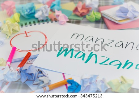 Spanish; Kids Writing Name of the Fruits for Practice (Translation; Apple) - stock photo