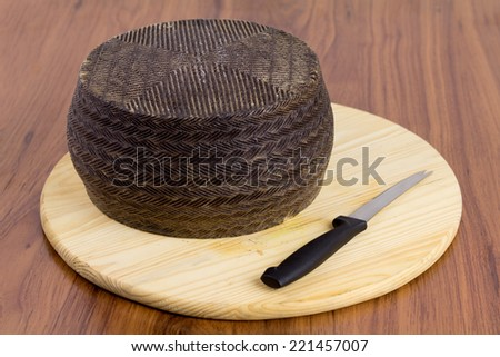 Spanish manchego cheese with a special cutting knife on a wooden board - stock photo