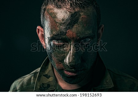 Spanish military with camouflage paint on face on black background - stock photo