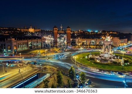 Spanish Square aerial view in Barcelona, Spain at night. This is the famous place with traffic light trails, fountain and Venetian towers, and National museum at the background. Blue sky - stock photo