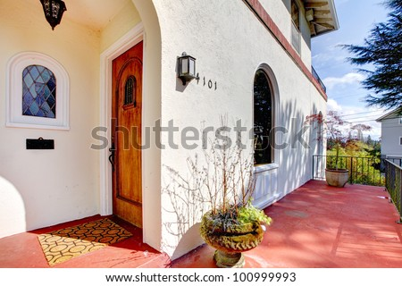 Spanish style white house with red concrete porch and front door. - stock photo