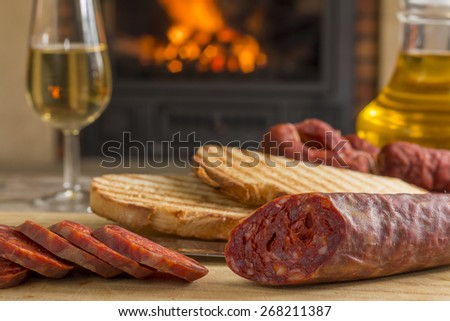 spanish tapa for brunch. Iberian chorizo, mature cheese, toasts, oil and white wine with fireplace at background - stock photo