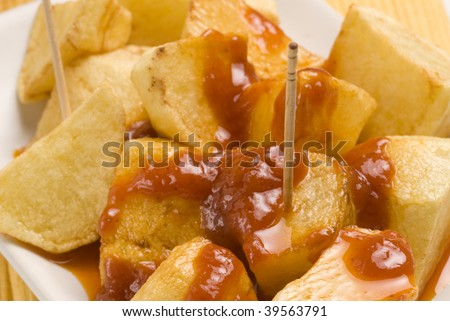 Spanish tapas. Bold potatoes in hot sauce. Typical appetizer. Closeup. Selective focus. Patatas bravas. - stock photo