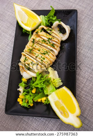 spanish tapas grilled squid decorated with lemons - stock photo