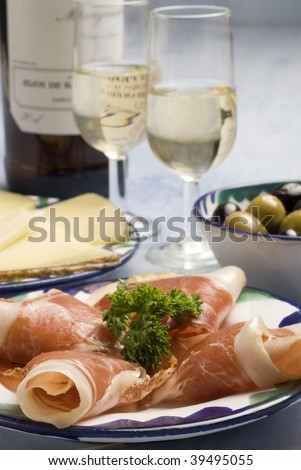 Spanish tapas. Sliced Iberian ham in a plate. Typical appetizer. Cheese, marinated olives and sherry wine on the background. - stock photo