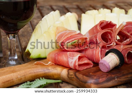 spanish tapas  - slices of cured pork ham jamon with melon and red wine - stock photo