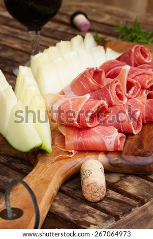 spanish tapas  - slices of cured pork  jamon with melon and wine - stock photo