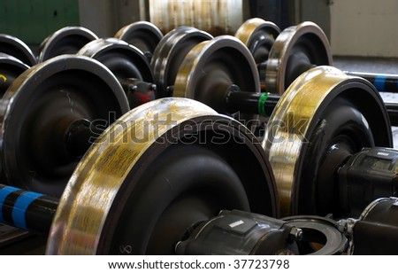 Spare railway wheels on the axle in a repair workshop - stock photo