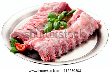 Spare ribs uncooked on stainless steel platter. Isolated on white. - stock photo