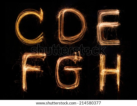 Sparkler firework light alphabet C-H - stock photo