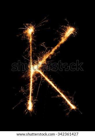 Sparkler firework light alphabet K (Capital Letters) at night background - stock photo