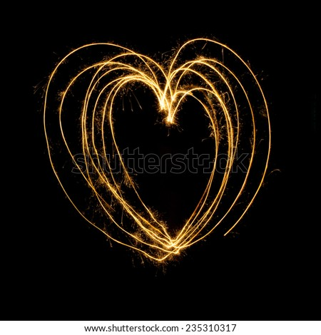 Sparkler firework light with heart shape isolated on black background. - stock photo
