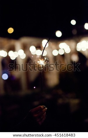 sparklers in the hand of a woman - stock photo