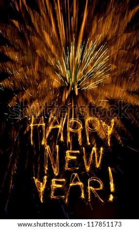 Sparklers write Happy New Year on golden fireworks burst - stock photo