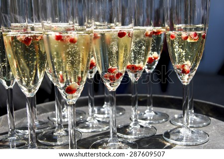 Sparkling champagne flutes on tray with pomegranate seeds. - stock photo