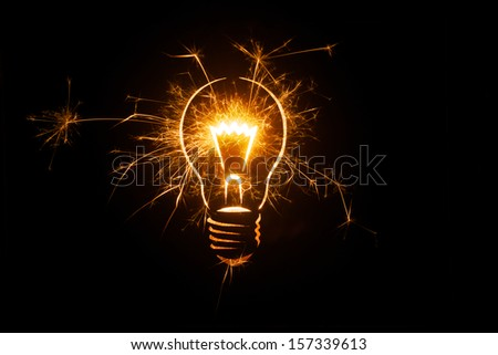 Sparkling light bulb on black background with ample copy space. - stock photo