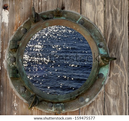 Sparkling ocean water seen through a rustic old porthole. - stock photo